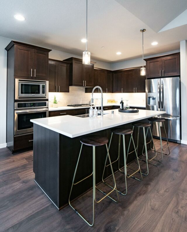 Here's a design take on one of our standard features: stained cabinetry. For a crisp look we chose contrasting white counters and subway tiles with this dark stain option. Contemporary brass barstools add the finishing touch. What do you think? Would you try this look in your kitchen? 